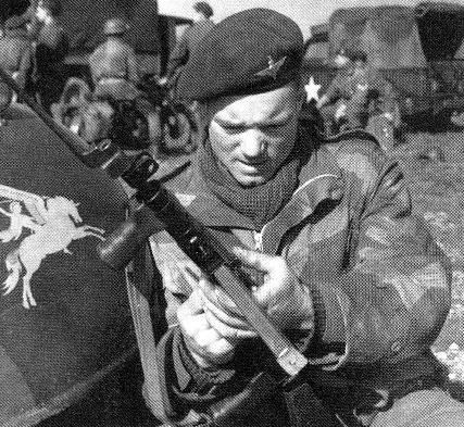 A British 6th Airborne Division paratrooper checks his Sten gun on March 24, 1944, before jumping into Germany.