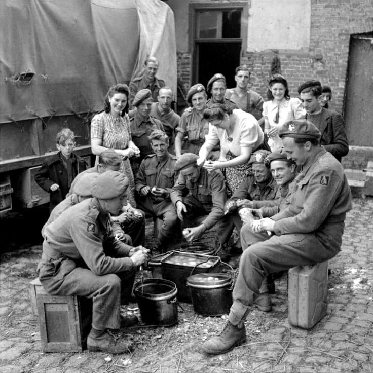 French civilians help British soldiers peel potatoes near the town of Saint-Pol-sur-Ternoise, Pas-de-Calais, France. 3 September 1944