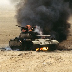 An Iraqi T-55 main battle tank burns after an attack by the 1st United Kingdom Armored Division during Operation Desert Storm.