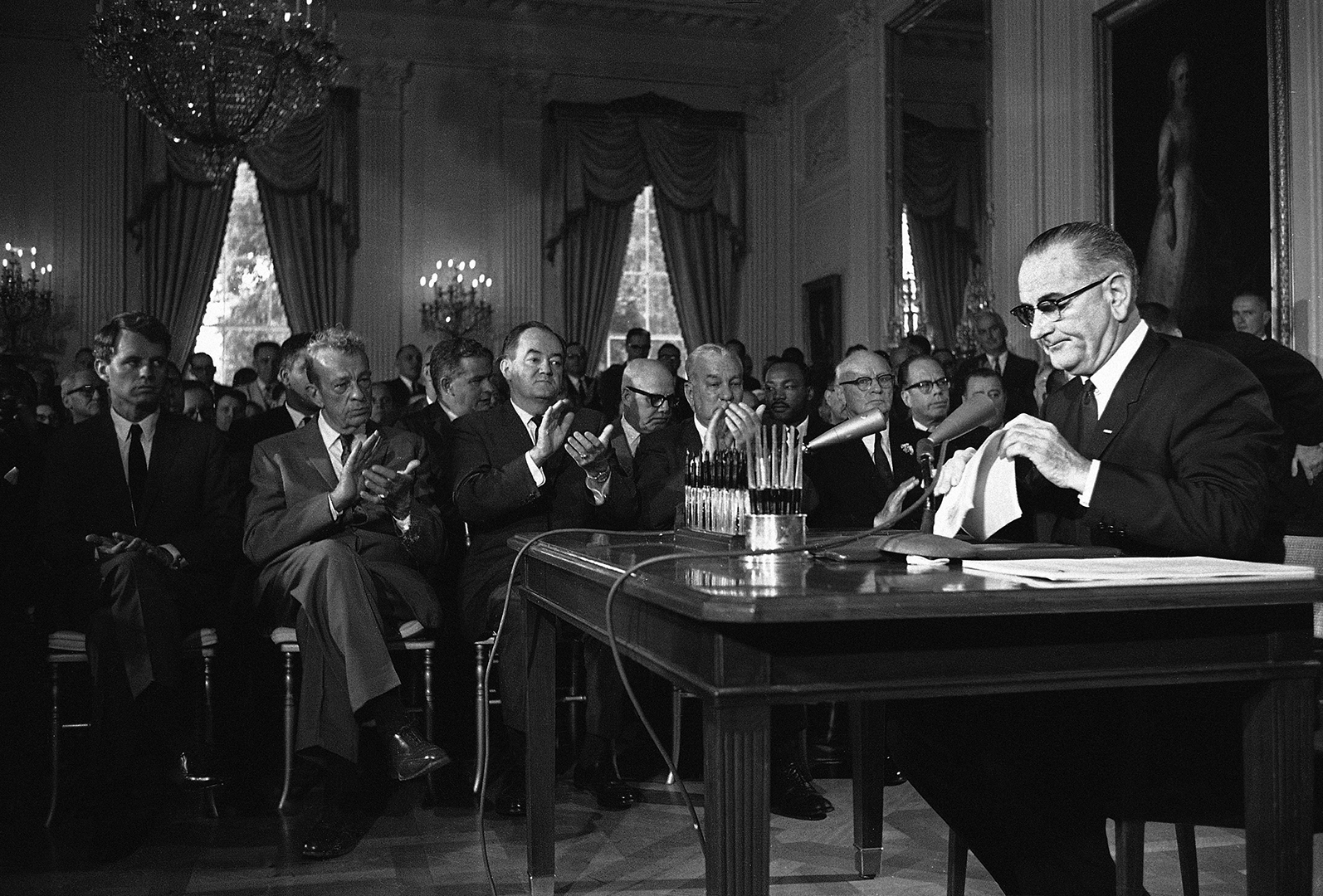 President Lyndon B. Johnson is applauded as he finished his speech in the White House in Washington on July 2, 1964, over a radio-TV network prior to signing the 1964 Civil Rights Bill. Front row from left: Atty. Gen. Robert F. Kennedy, Sen. Everett M. Dirksen, R-Ill; Sen. Hubert H. Humphrey, D-Minn.; Rep. Charles Halleck, R-Ind.; and Rep. Emanuel Celler, D-N.Y. Second row: Whitney Young, behind Dirksen, executive director, National Urban League; Rep. Richard Bolling, D-Mo.; Dr. Martin Luther King, Southern Christian Leadership Conference; and Sen. Thomas H. Kuchel, R-California. (AP Photo)