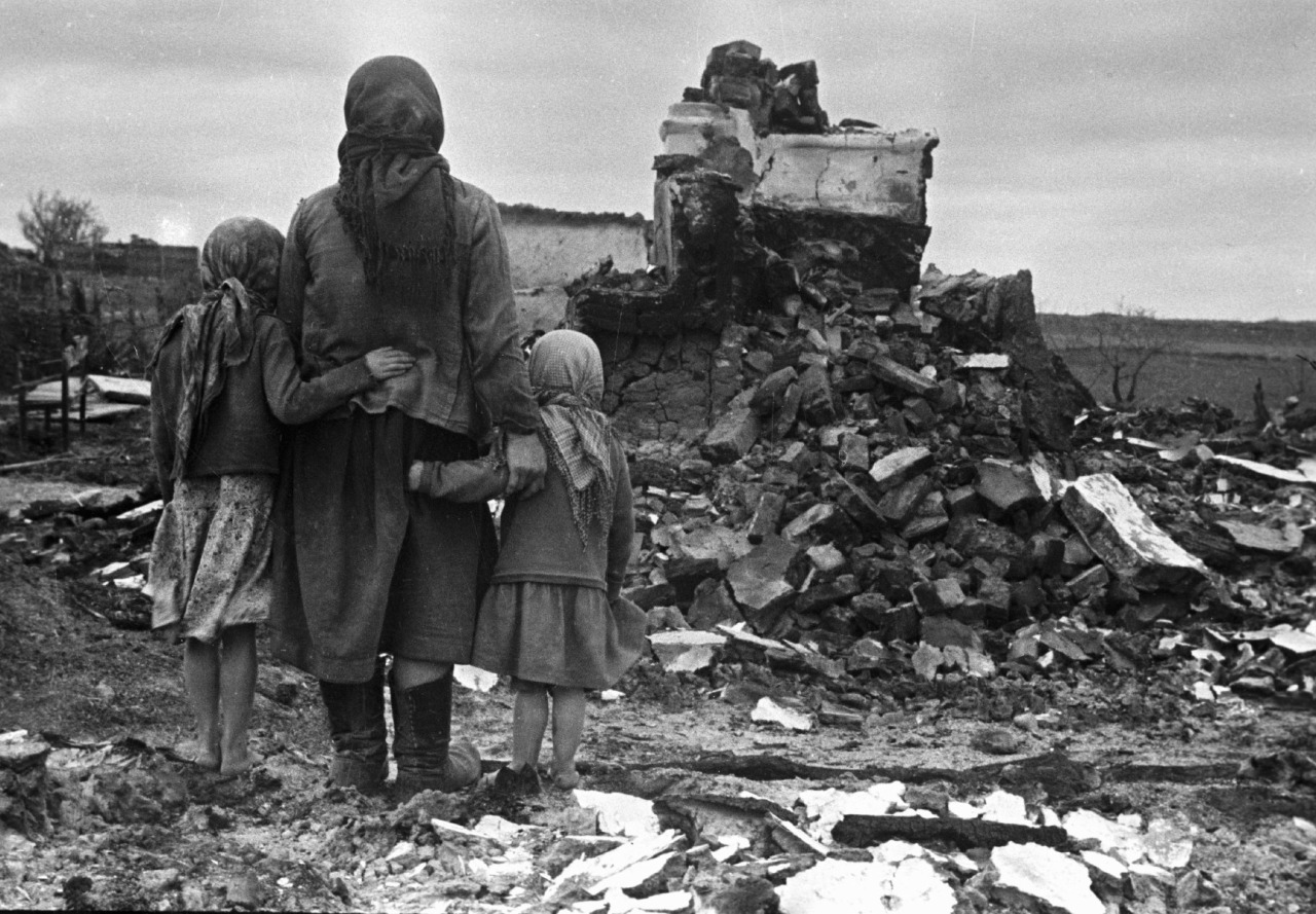 A Russian mother and her two young daughters survey the destruction of their home after the Second Battle of Smolensk. Autumn, 1943.